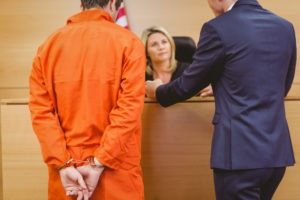 lawyer with defendant speaking to judge in court